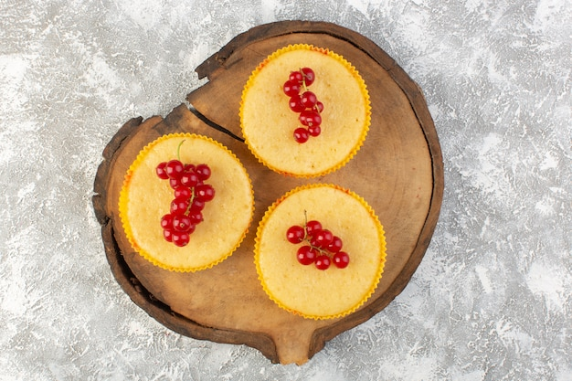 Draufsicht-kuchen mit preiselbeeren lecker und perfekt auf dem hölzernen hintergrundkuchen gebacken, kekszucker süß