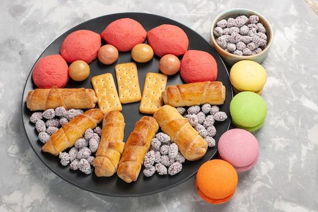 Draufsicht kuchen und bagels mit bonboncrackern und macarons auf weißer oberfläche kuchenplätzchenplätzchenzuckersüßkuchen