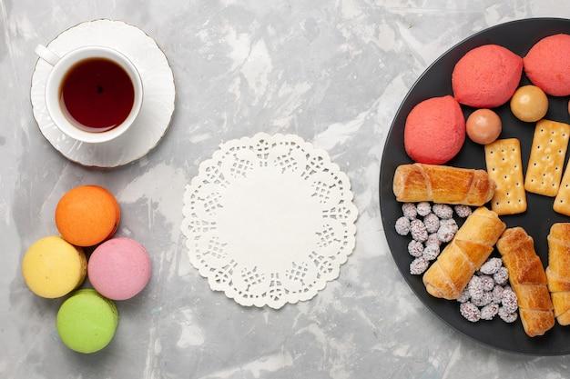 Draufsicht kuchen und bagels mit süßigkeiten cracker macarons und tasse tee auf weißem hintergrund kuchen keks keks zucker süße torte