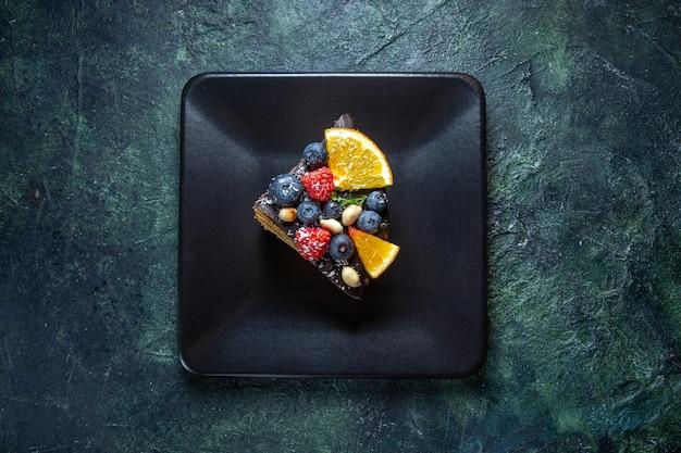 Draufsicht kuchenscheibe köstlichen schokoladenkuchen mit früchten innerhalb platte auf dunkelheit