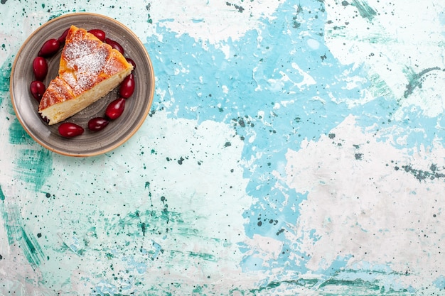 Draufsicht-kuchenscheibe mit frischen roten hartriegeln auf hellblauem hintergrundfruchtkuchen backen kuchenkuchenzuckerkeks süß