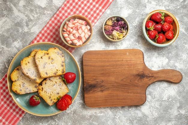 Draufsicht-kuchenscheiben mit frischen erdbeeren auf süßer tortenfrucht der weißen oberfläche