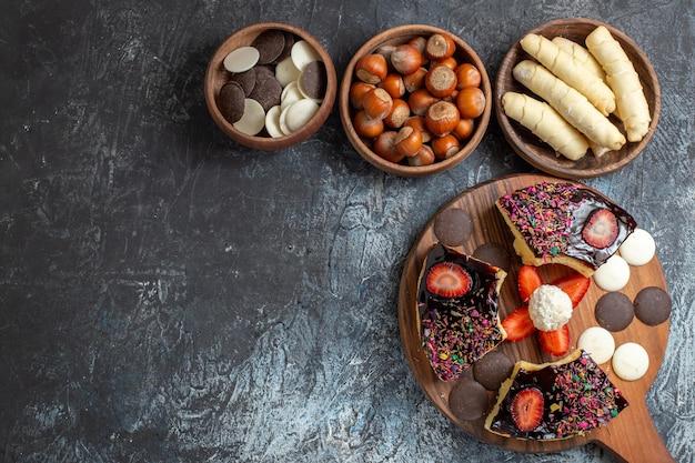 Draufsicht kuchenscheiben mit nüssen und süßigkeiten auf dunkler oberfläche