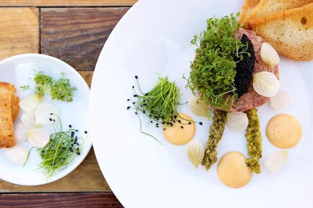 Draufsicht kulinarische vorspeise mit kaviar, pastete, toast, zwiebeln und einer auswahl an dressings