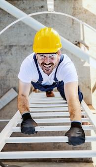Draufsicht lächelnder kaukasischer arbeiter in overalls und mit helm auf kopf, der auf öltank in raffinerie klettert.