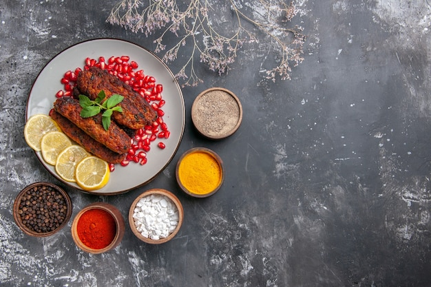 Draufsicht lange fleischkoteletts mit zitrone und granatäpfeln