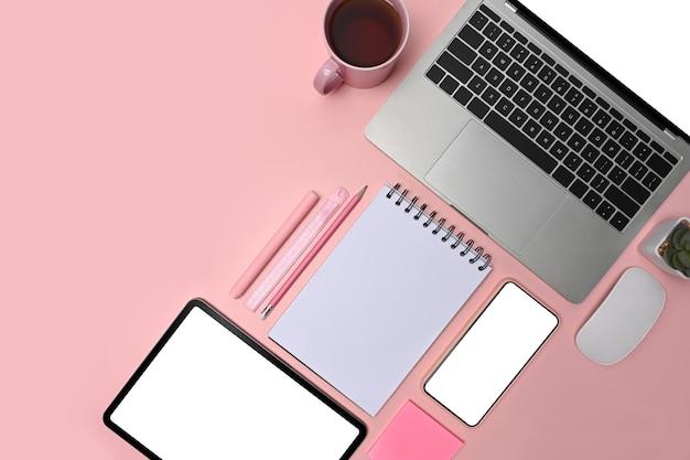 Draufsicht laptop, tablet, smartphone, brille und kaffeetasse auf rosa hintergrund.