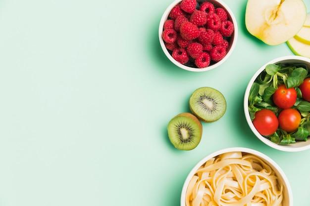 Draufsicht lebensmittelbehälter mit himbeeren, salat und nudeln mit kopierraum