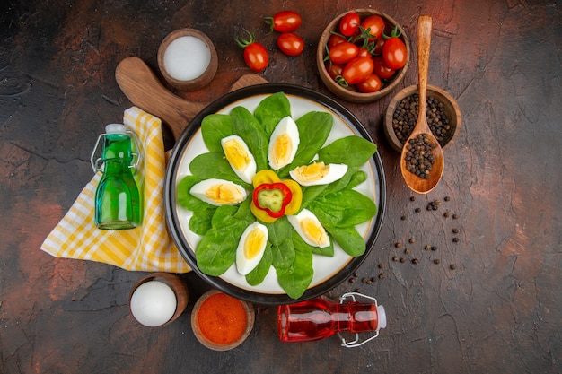 Draufsicht lecker gekochte eier mit gewürzen und tomaten auf dunklem tisch