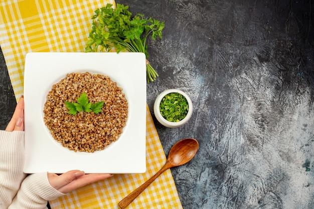 Draufsicht lecker gekochter buchweizen-innenteller mit grüns auf hellgrauem tisch
