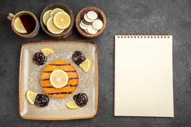 Draufsicht lecker süßer kuchen mit zitronenscheiben und tasse tee auf dem grauen hintergrund kuchenkuchen keks süße kekse