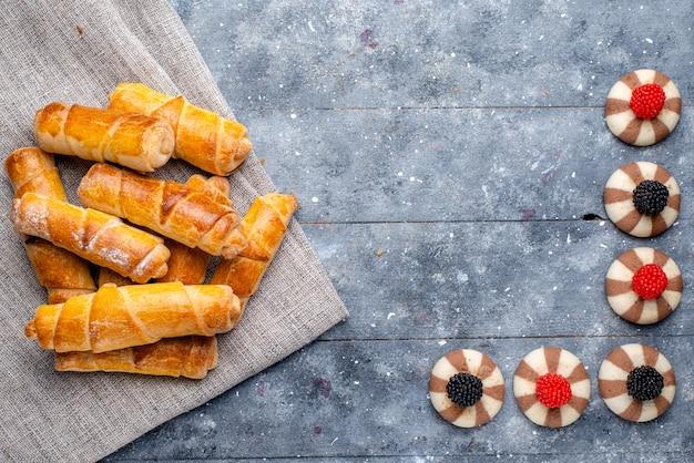 Draufsicht leckere armreifen mit füllung zusammen mit keksen auf dem grauen hintergrundkuchen backen keks süßer zucker