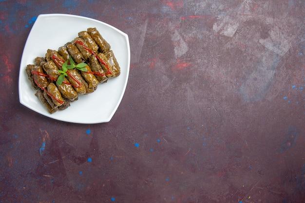 Draufsicht leckere blatt-dolma-hackfleischschale innerhalb der platte auf der dunkelheit
