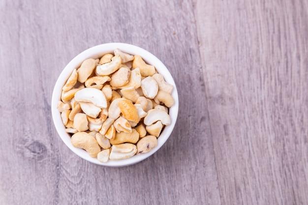 Draufsicht leckere cashewnüsse in weißer schüssel auf holztisch, platz für text