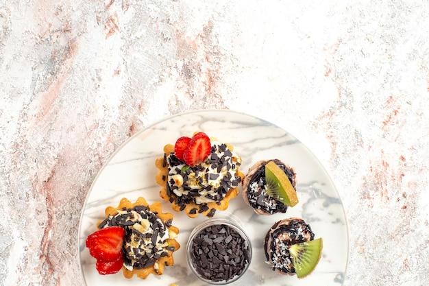 Draufsicht leckere cremige kuchen kleine desserts für tee mit schokoladenstückchen auf weißer oberfläche obstkuchen sahnekeks kuchentee