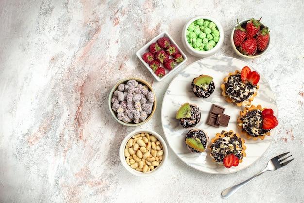 Draufsicht leckere cremige kuchen mit beeren und bonbons auf weißer oberfläche keks-frucht-kuchen-sahne-torte-tee-kekse
