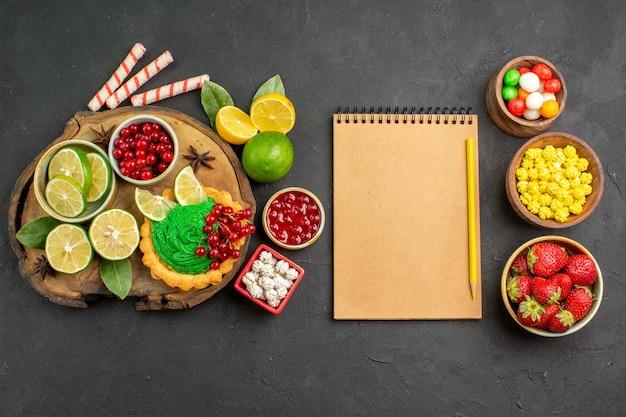 Draufsicht leckere cremige torte mit süßigkeiten und früchten auf dem süßen hintergrund süßer kekskeks