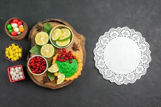 Draufsicht leckere cremige torte mit süßigkeiten und früchten auf dunklem hintergrund kekskeks süß
