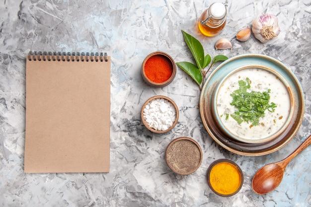 Draufsicht leckere dovga-joghurtsuppe mit gewürzen auf weißem bodengericht milchsuppe molkerei