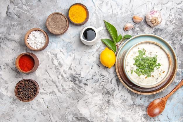 Draufsicht leckere dovga-joghurtsuppe mit gewürzen auf weißem milchsuppengericht molkerei
