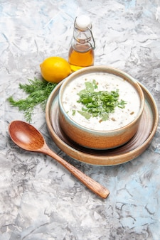 Draufsicht leckere dovga-joghurtsuppe mit grüns auf hellweißem suppengericht milchprodukte
