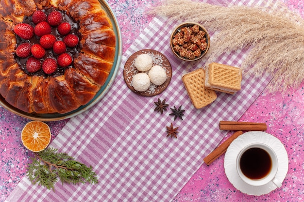 Draufsicht leckere erdbeerkuchen mit waffeln und tasse tee auf rosa