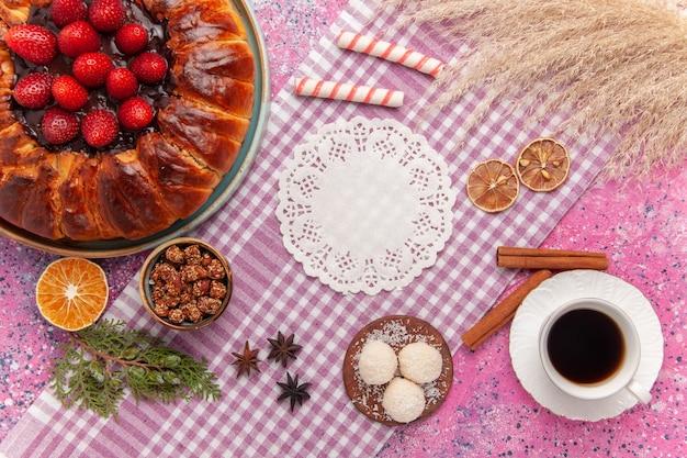 Draufsicht leckere erdbeerkuchen mit zimt und tasse tee auf rosa