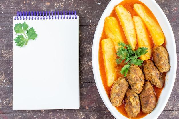 Draufsicht leckere fleischkoteletts gekocht zusammen mit kartoffeln und soße innerhalb platte mit notizblock auf dem braunen hintergrund fleischkartoffelgericht mahlzeit abendessen