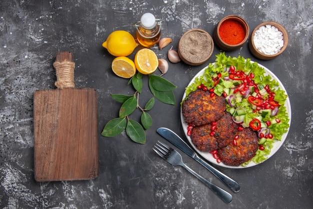 Draufsicht leckere fleischkoteletts mit gemüsesalat auf dem grauen hintergrundfoto-nahrungsmittelmahlzeitgericht