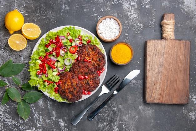 Draufsicht leckere fleischkoteletts mit salat und gewürzen auf grauem schreibtischfoto-nahrungsmittelgericht