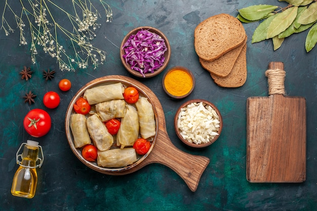Draufsicht leckere fleischmahlzeit gerollt mit kohl und tomaten genannt dolma mit olivenöl und brot auf dunkelblauem schreibtisch