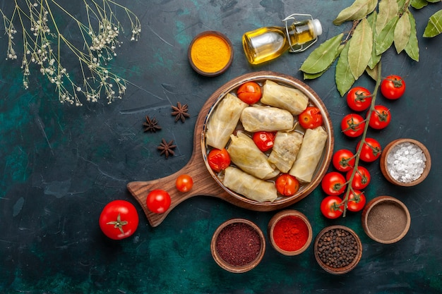 Draufsicht leckere fleischmahlzeit in kohl mit gewürzen und frischen tomaten auf dunkelblauem schreibtisch gerollt
