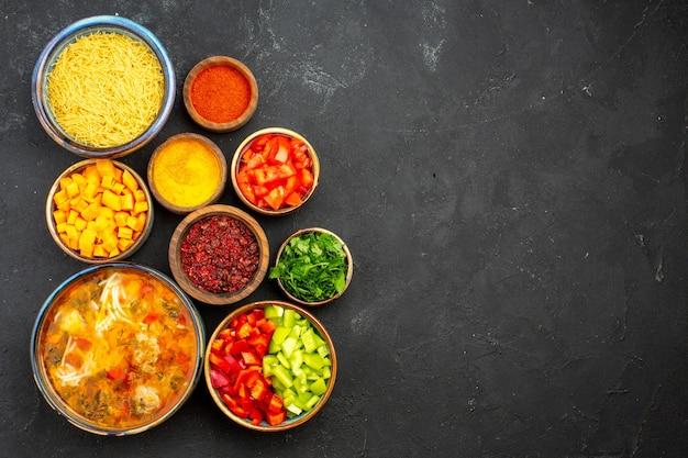 Draufsicht leckere fleischsuppe mit gemüse und gewürzen auf dem grauen hintergrund salatsuppe mahlzeit essen abendessen
