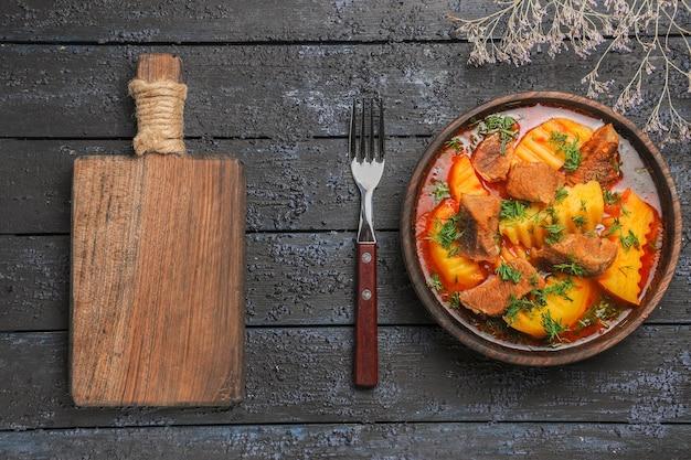 Draufsicht leckere fleischsuppe mit gemüse und kartoffeln auf dunklem schreibtisch