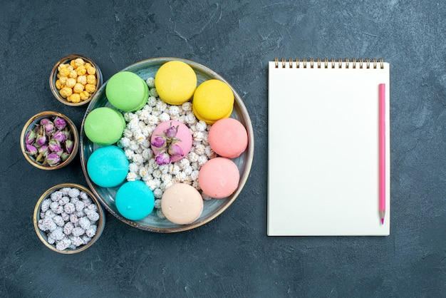 Draufsicht leckere französische macarons mit bonbons auf grau