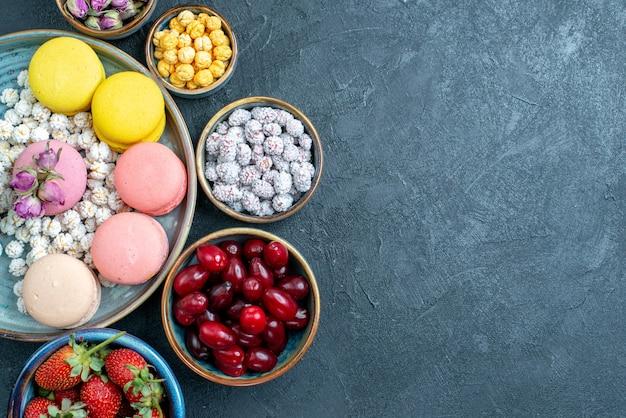 Draufsicht leckere französische macarons mit früchten auf grau