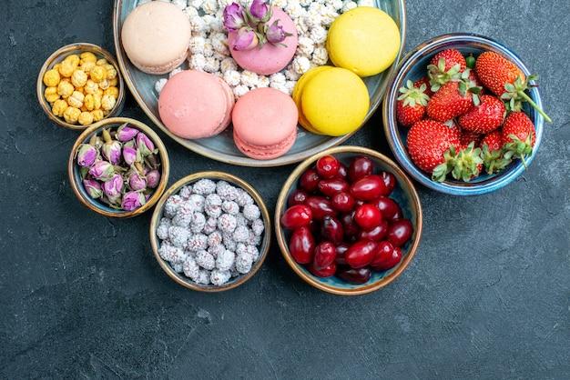 Draufsicht leckere französische macarons mit süßigkeiten und früchten auf grau
