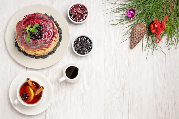 Draufsicht leckere gelee-pfannkuchen mit rosinen-fruchtgelee und tasse tee auf hellweiß