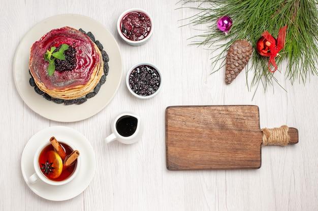 Draufsicht leckere gelee-pfannkuchen mit rosinen und tasse tee auf weiß