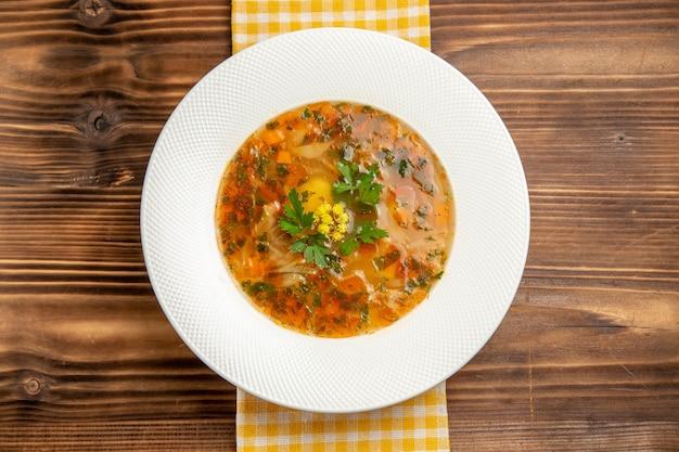 Draufsicht leckere gemüsesuppe mit gemüse auf brauner hölzerner tischsuppe lebensmittelgemüsegewürz