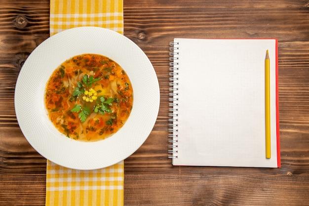 Draufsicht leckere gemüsesuppe mit gemüse auf der braunen hölzernen schreibtischsuppe essen gemüsewürzmittel