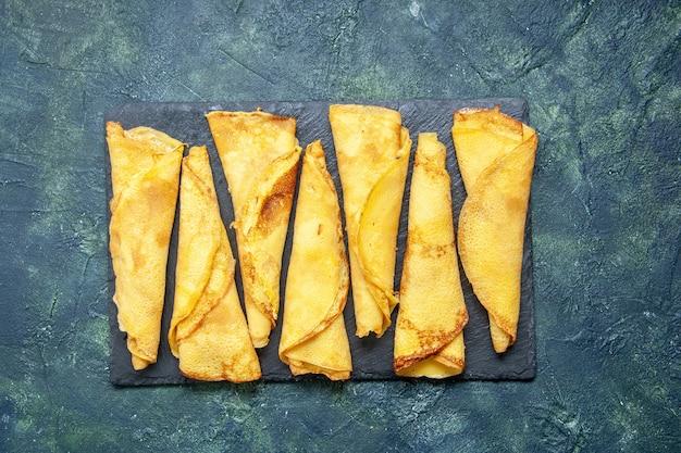 Draufsicht leckere gerollte pfannkuchen, die auf dem dunklen hintergrundfarbe-mahlzeitkuchen-fleisch-gebäck-teig-kuchen süßer heißer kuchen gesäumt sind
