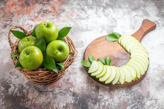 Draufsicht leckere grüne äpfel mit geschnittenen früchten auf dem hellen hintergrund