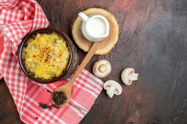 Draufsicht leckere julienne in schüssel rohe pilze milchschüssel auf holzbrett schwarzer pfeffer in holzlöffel rot-weiß kariertes küchentuch auf braunem tisch