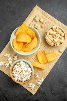 Draufsicht leckere käsechips mit verschiedenen snacks für die filmzeit auf dem dunklen hintergrund