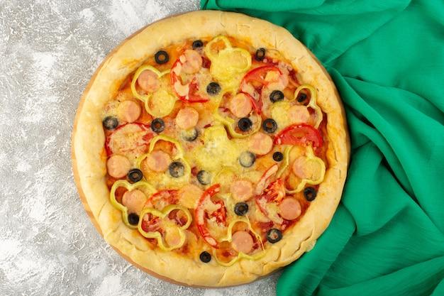 Draufsicht leckere käsige pizza mit würstchen der schwarzen oliven und roten tomaten auf dem grauen hintergrund mit grünem tissue-fastfood-italienischem teigmehlauflauf