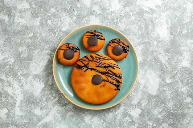 Draufsicht leckere kakaokuchen mit schokoladenglasur in der platte auf einem weißen oberflächenkuchen-keks-dessert süßer kekskuchen