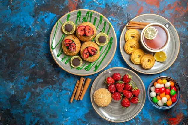 Draufsicht leckere kekse mit einer tasse tee und bonbons auf der süßen frucht des blauen kekses