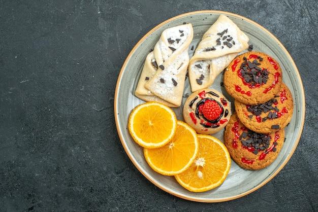Draufsicht leckere kekse mit fruchtigem gebäck und orangenscheiben auf dunklem hintergrund obst süßer kuchen kuchen tee zucker