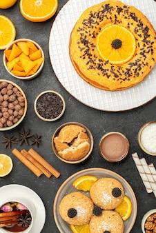 Draufsicht leckere kekse mit süßem kuchen und tasse tee auf dunkler oberfläche kuchenkuchen zucker dessert keks tee
